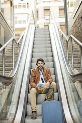 Smiling man with cell phone, headphones and suitcase sitting on escalator - JASF01334