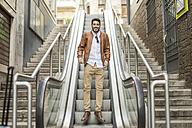 Smiling man jumping on escalator - JASF01337