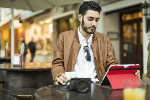 Young man using tablet at outdoor cafe - JASF01340