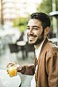 Smiling man drinking juice at outdoor cafe - JASF01343