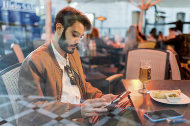 Young man using tablet at outdoor bar - JASF01352