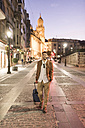 Smiling man with suitcase at night in the city - JASF01355