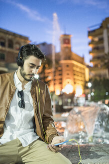 Man with headphones and cell phone at a fountain at night - JASF01358