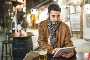 Young man using tablet at outdoor bar - JASF01361
