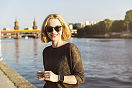 Germany, Berlin, portrait of smiling young woman wearing sunglasses and smartwatch - TAMF00858