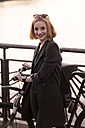 Portrait of smiling young woman with bicycle at evening twilight - TAMF00879