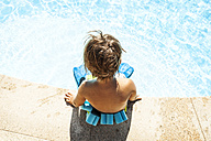 Back view of little boy with floating belt sitting at pool edge - VABF00847