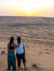 Oman, Al Raka, two young women standing arm in arm on a desert dune watching sunset - AMF05103