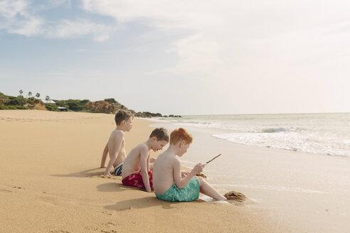 Three boys sitting on the beach - NMSF00004
