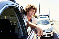 Smiling young man looking out of car window - WESTF21977