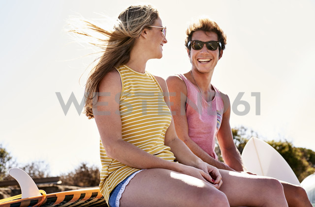 Smiling young couple sitting outdoors - WESTF21998