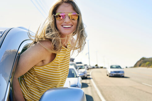 Happy young woman leaning out of car window - WESTF22004