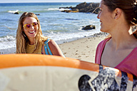 Two happy women carrying surfboards on the beach - WESTF22022