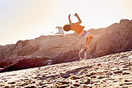 Young man on the beach doing a somersault - WESTF22028