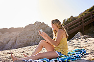 Young woman checking cell phone on the beach - WESTF22031