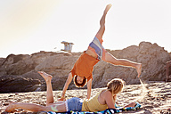 Young man with woman on the beach doing a cartwheel - WESTF22037