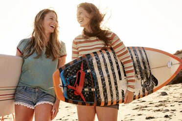 Two happy women carrying surfboards on the beach - WESTF22046