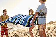 Happy friends spreading out towel on the beach - WESTF22052