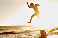 Playful man jumping on the beach at sunset - WESTF22058