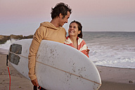 Smiling young couple on the beach carrying surfboard - WESTF22076