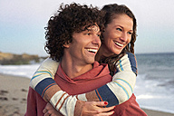 Happy young man carrying girlfriend piggyback on the beach - WESTF22079