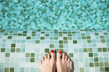 Woman's feet at poolside - CHPF00355