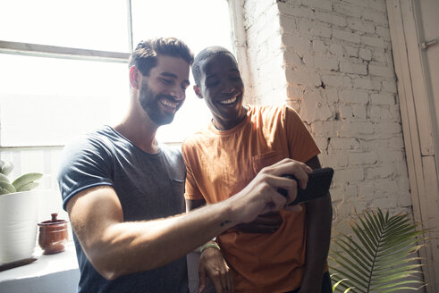 Two happy young men with cell phone in a loft - WESTF22081