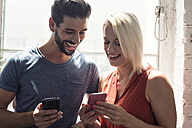 Happy young couple with cell phones at the window - WESTF22087
