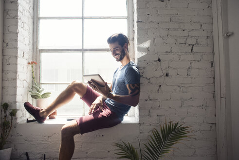 Smiling young man sitting on windowsill looking at tablet - WESTF22093