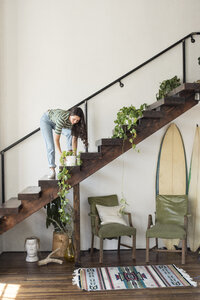 Young woman on stairs in a loft caring for potted plant - WESTF22099