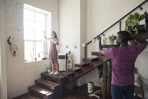 Young couple decorating loft with fairylights - WESTF22105