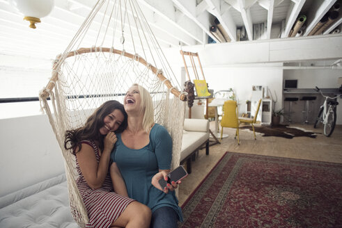 Two happy young women in hammock with cell phone - WESTF22108