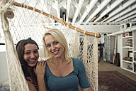Portrait of two smiling young women in hammock - WESTF22111