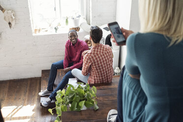 Two men sitting on stairs in a loft with woman using cell phone - WESTF22114