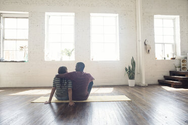 Young couple sitting on carpet in a loft - WESTF22120