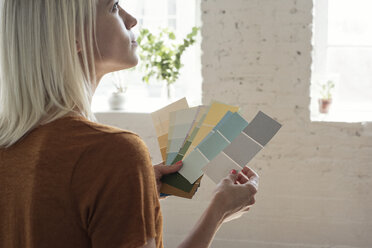 Young woman in a loft thinking about color samples - WESTF22123