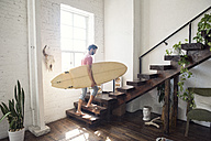 Young man carrying a surfboard on stairs in a loft - WESTF22129