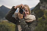 Young woman taking picture outdoors - KKAF00075
