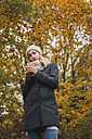 Young woman with hot beverage in autumn forest - KKAF00078
