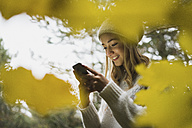 Smiling young woman with cell phone in autumn forest - KKAF00093