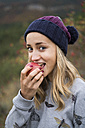 Portrait of smiling young woman eating an apple outdoors - KKAF00096