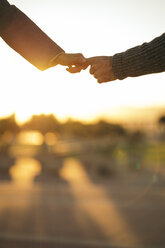 Couple in love holding hands at sunset, partial view - KKAF00141