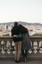 Spain, Barcelona, back view of couple arm in arm looking at the city - KKAF00147