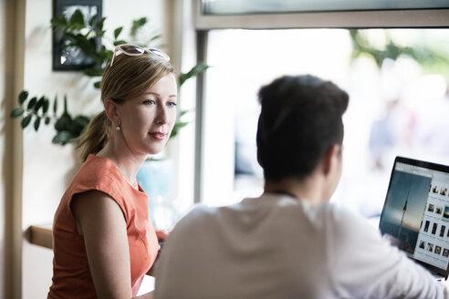 Woman looking at teenage boy using laptop - TAMF00887
