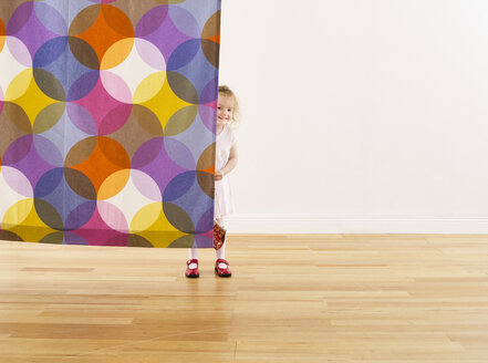 Smiling little girl hiding behind curtain - FSF00605