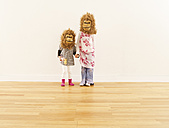 Two girls wearing monkey masks standing hand in hand in front of white wall - FS00620