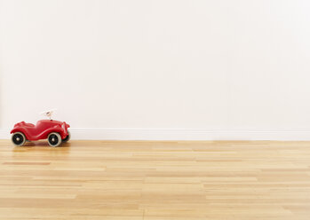 Red pedal car standing on parquet - FSF00629