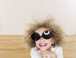 Portrait of smiling girl with blond ringlets wearing oversized sunglasses - FSF00641