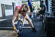 Woman preparing barbell in gym - KIJF00917