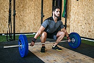 Man ready to lift barbell in gym - KIJF00920